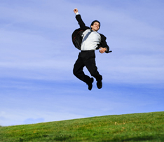 photo shows man in a suit jumping in the air celebrating getting his new job